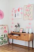Deko in Rosa und botanische Zeichnungen um altes Sideboard