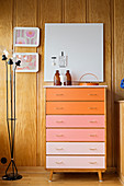 Chest of drawers with drawers in colour gradient against wood-panelled walls