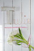 White tulips and 'Tulip' written on wooden wall