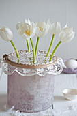 White tulips in vase with lace doily used as flower grid