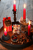 Winterdeko mit roten Kerzen und Katzenfigur auf einem Tablett