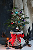 Small Christmas tree in fabric sack, candle and pine cones