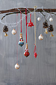 Branch adorned with Christmas-tree decorations and pine cones with tassels