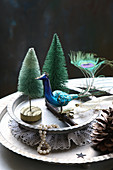 Winter arrangement of peacock figurine and miniature trees on metal plates
