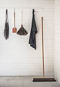 Cleaning utensils and dustpan hung from coat rack on white-painted wooden wall