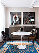 Classic table in dining area with industrial-style furniture and two framed ethnic headdresses on wall