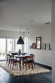 Dark chairs around oval table in dining room with stone-flagged floor