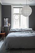 Schlafzimmer in Weiß und Grau mit Papierlampion überm Bett