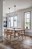 Designer chairs around dining table in front of open-plan kitchen in period building