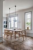 Designerstühle am Esstisch vor der offenen Küche im Altbau