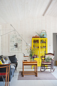 Yellow display case and old rocking chair in living room