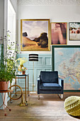 Armchair and pictures against wall with pale blue wainscoting