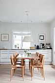 Pale wooden dining set in front of white kitchen counter