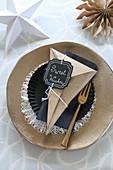 DIY-Papiertüte mit Botschaft als Gedeck zu Weihnachten auf goldenem Teller