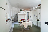 Fitted kitchen units, round dining table and stairs leading to upper level in open-plan interior