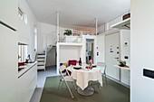 Offener Wohnraum in Weiß mit Einbauküchenzeile, rundem Esstisch und Treppe zur oberen Ebene