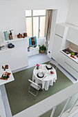 View from gallery down into white interior with kitchen counter and dining table
