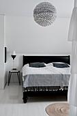 Polka-dot paper lampshade above black bed in bedroom