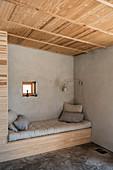Sitzecke mit Bank in einer Nische mit grauer Wand und Holzdecke
