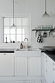 Sink in black-and-white kitchen with lattice window