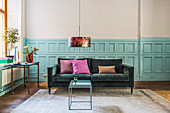 Emerald-green sofa against pale blue panelled wainscoting in living room