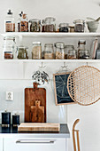 Storage jars on two shelves with hooks below in kitchen
