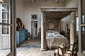 Schlafzimmer im französischen Stil mit massivem Himmelbett aus Holz