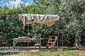 Alter Tisch auf Terrasse mit Sonnensegel im mediterranen Garten