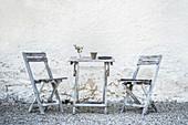 Rustikaler Holztisch und Stühle auf Kiesboden