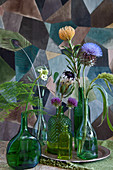 Artichoke flower, amaranth, pincushion protea, alliums, star-of-Bethlehem and asparagus fern in bottles