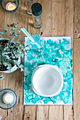Handmade place mats with turquoise watercolour effect on wooden table