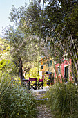 Blick durch mediterranen Garten auf Terrassenplatz vor Haus