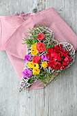 Wicker love-heart decorated with real geraniums and colourful paper flowers on gingham cloth