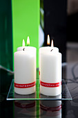 Modern Advent arrangement of labelled pillar candles on glass plate