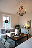 Christmas decorations and chandelier in classic, white living room