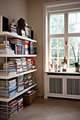 Books stacked on shelves next to window above radiator cover