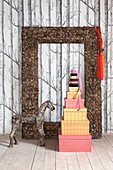 Stacked gift boxes, horse sculpture and picture frame in front of wallpaper with pattern of trees