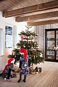 Kinder mit Weihnachtsmützen vorm Weihnachtsbaum im Wohnzimmer