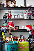 Two children wearing Christmas hats placing wrapped gifts on shelves