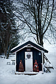 Festively decorated shed in snowy garden