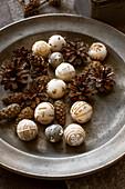 Winterliche Dekoration aus bestickten Filzkugeln und Zapfen