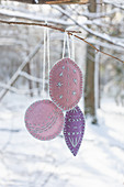 Handmade, embroidered felt decorations hung from branch in snowy garden