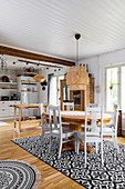 Dining table and country-house kitchen in open-plan interior in Bohemian style