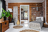 Chaise chair in rustic living room with brick and wooden walls