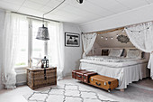Bed with valance under sloping ceiling in Bohemian-style bedroom