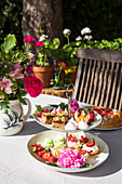 Pastries, fruit and flowers on cake stand in summery garden