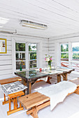 Benches around table with glass top in summery wooden house