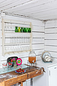 Glasses on plate rack in kitchen with board walls and workbench