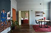 Runder Esstisch im hellblauen Wohnraum mit Blick ins Schlafzimmer
