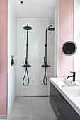 Two shower heads in walk-in shower in pink, modern bathroom